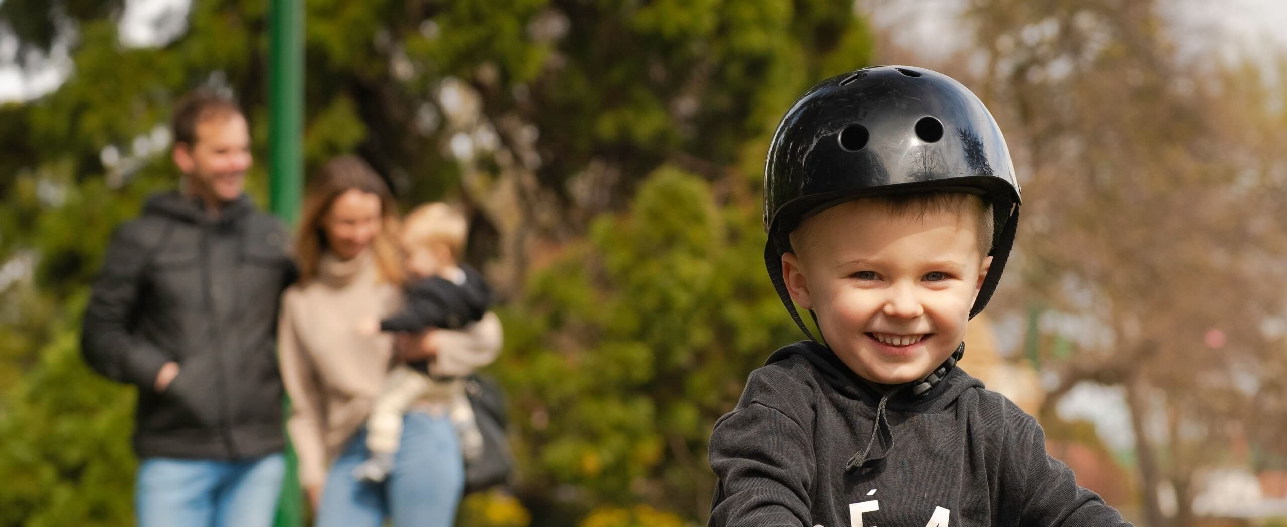 smiling toddler wearing a helmet as the family stand in the background